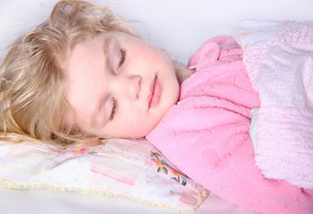 A little girl sleeping in bed with her pillow and blanket.